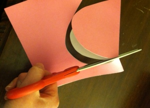 cutting heart shape on pink paper
